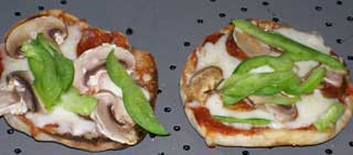photo showing two muffin pizzas.