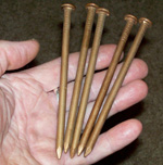 Photo of spike - 5 inch solid copper nails - held.