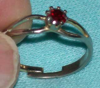 Photo of Ruby colored Glass gem ring - Costume Jewelry, used, being held.