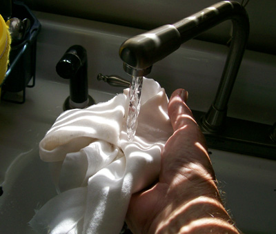 Photo of a piece of muslin being wetted. It will be used to filter the juice once good and wet