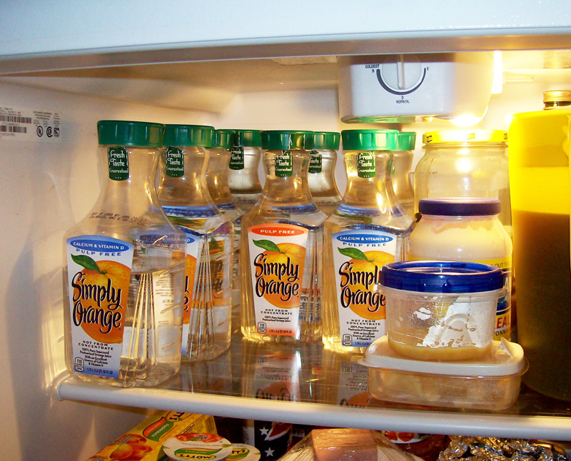 photo of inside of the refrigerator showing 8 half gallon jugs of sap.