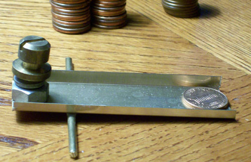 Photo of a home made penny sorter with a copper penny which dipped down.