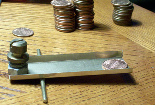 Photo of a home made penny sorter with a zinc penny at the front of the scale