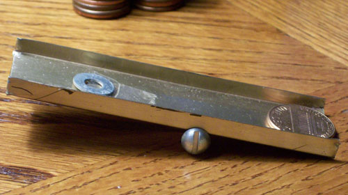 Photo of a very simple home made penny sorter with a copper penny at the front which dipped down.