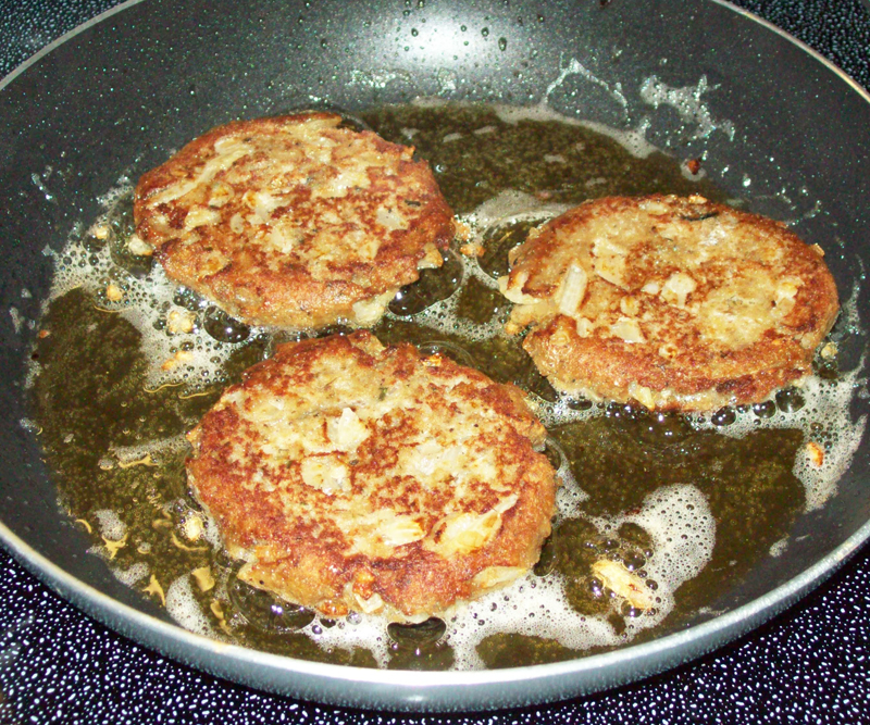 photo of three sardine patties frying.